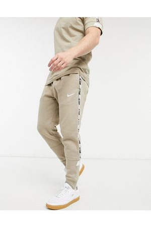 Nike Repeat Pack taping cuffed joggers in stone