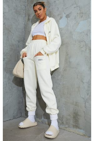 PRETTYLITTLETHING Cream Exclusive Badge Detail Pocket Thigh Joggers
