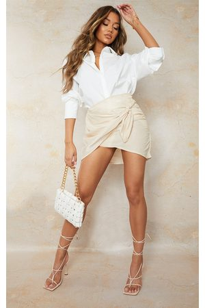 PRETTYLITTLETHING Cream Woven Shimmer Wrap Over Tie Waist Mini Skirt